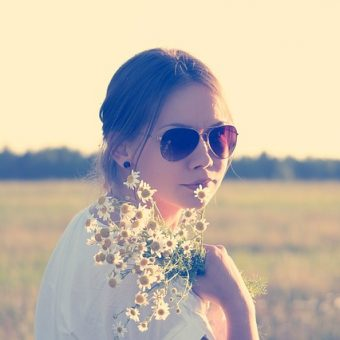 Girl-with-sunglasses-has-flowers-in-her-hand