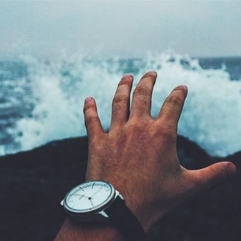 Man-with-watch-on-hand-admiring-the-waves