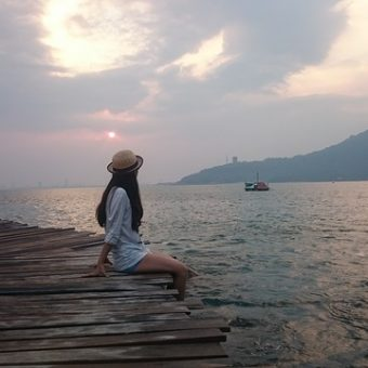 Girl-sits-on-wood-and-looks-at-the-sea