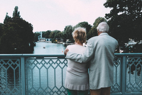 old-couple-hugging-on-bridge