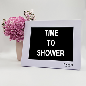 "Original Dawn Clock shown on a table with the ""Time to shower"" reminder on the screen. This is ideal for all ages and proved essential for NDIS participants, people living with Dementia, people living with a disability and seniors."