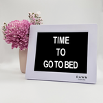 "Original Dawn Clock shown on a table with the ""Time to go to bed"" reminder on the screen. This is ideal for all ages and proved essential for NDIS participants, people living with Dementia, people living with a disability and seniors."