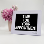 "Original Dawn Clock shown on a table with the ""Time for your appointment"" reminder on the screen. This is ideal for all ages and proved essential for NDIS participants, people living with Dementia, people living with a disability and seniors."