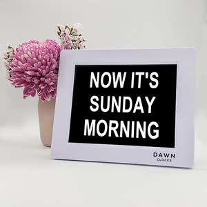 "Original Dawn Clock shown on a table ""Now its Sunday Morning"" on the screen. This is the moment mode."