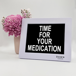 "Original Dawn Clock shown on a table with the ""Time for your medication"" reminder on the screen. This is ideal for all ages and proved essential for NDIS participants, people living with Dementia, people living with a disability and seniors."