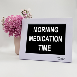 "Original Dawn Clock shown on a table with the ""Morning medication time"" reminder on the screen. This is ideal for all ages and proved essential for NDIS participants, people living with Dementia, people living with a disability and seniors."