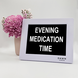 "Original Dawn Clock shown on a table with the ""Evening medication time"" reminder on the screen. This is ideal for all ages and proved essential for NDIS participants, people living with Dementia, people living with a disability and seniors."