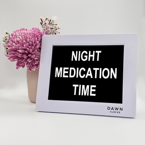 "Original Dawn Clock shown on a table with the ""Night medication time"" reminder on the screen. This is ideal for all ages and proved essential for NDIS participants, people living with Dementia, people living with a disability and seniors."