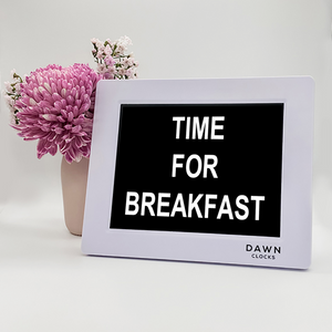 "Original Dawn Clock shown on a table with the ""Time for breakfast"" reminder on the screen. This is ideal for all ages and proved essential for NDIS participants, people living with Dementia, people living with a disability and seniors."