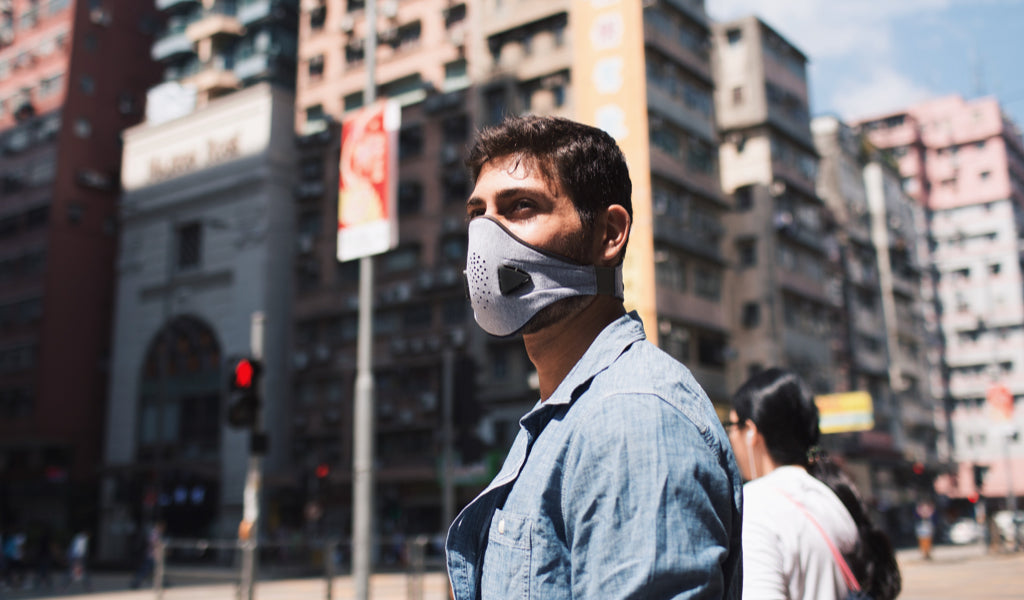 man wearing akmon air pollution facemask in the street