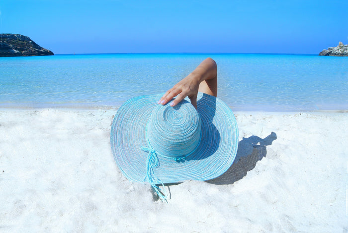 woman on white sand beach blue hat