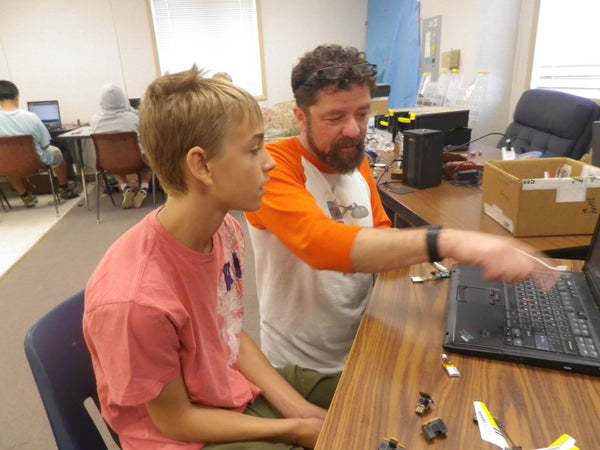 dr. george albercook works with a young man at rocks and robots summer camp