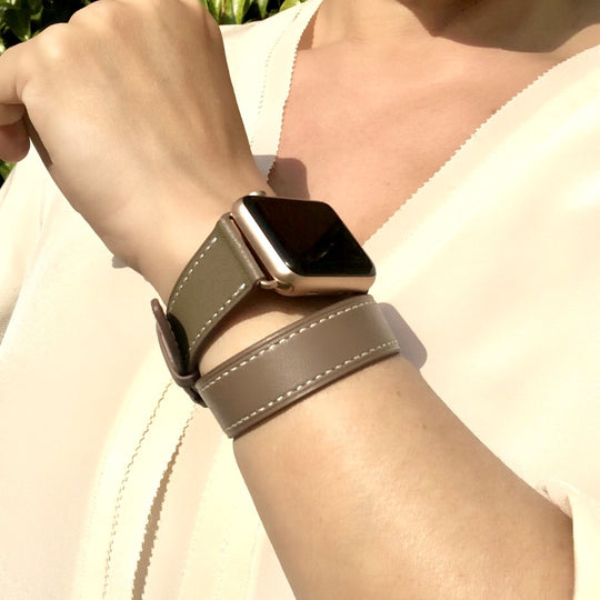 Hazel Brown Double Wrap Apple Watch Leather Band by Juxli Home.  Handmade, stylish leather strap with rose gold hardware on a 40mm Apple watch on a canvas with a black and gray painting.