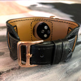 Black Apple Watch Leather Cuff by Juxli Home.  Handmade, stylish leather strap with rose gold hardware on a 40mm Apple watch on a canvas with a black and gray painting.