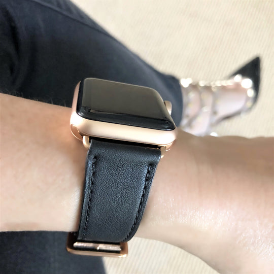 Black Apple Watch Leather Band by Juxli Home.  Handmade, stylish leather strap with rose gold hardware on a 40mm Apple watch on a canvas with a black and gray painting.