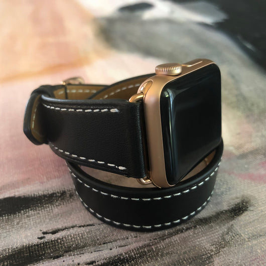 Black Double Wrap Apple Watch Leather Band with White Stitching by Juxli Home.  Handmade, stylish leather strap with rose gold hardware on a 40mm Apple watch on a canvas with a black and gray painting.
