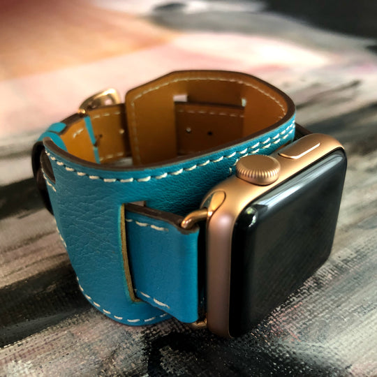 Cyan Blue Apple Watch Leather Cuff by Juxli Home.  Handmade, stylish leather strap with rose gold hardware on a 40mm Apple watch on a canvas with a black and gray painting.