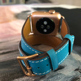 Cyan Blue Double Wrap Apple Watch Band by Juxli Home.  Handmade, stylish leather strap with rose gold hardware on a 40mm Apple watch on a canvas with a black and gray painting.