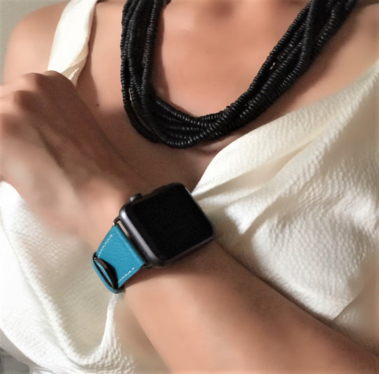 Cyan Blue Apple Watch Band by Juxli Home.  Handmade, stylish leather strap with rose gold hardware on a 40mm Apple watch on a canvas with a black and gray painting.
