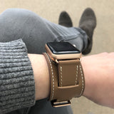 Caramel Brown Apple Watch Leather Cuff by Juxli Home.  Handmade, stylish leather strap with rose gold hardware on a 40mm Apple watch on a canvas with a black and gray painting.