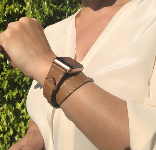 Caramel Brown Double Wrap Apple Watch Leather Band by Juxli Home.  Handmade, stylish leather strap with rose gold hardware on a 40mm Apple watch on a canvas with a black and gray painting.