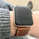 Cognac Brown Apple Watch Leather Band by Juxli Home.  Handmade, stylish leather strap with rose gold hardware on a 40mm Apple watch on a canvas with a black and gray painting.