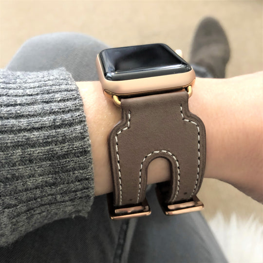 Chocolate Brown Double Buckle Apple Watch Leather Cuff by Juxli Home.  Handmade, stylish leather strap with rose gold hardware on a 40mm Apple watch on a canvas with a black and gray painting.