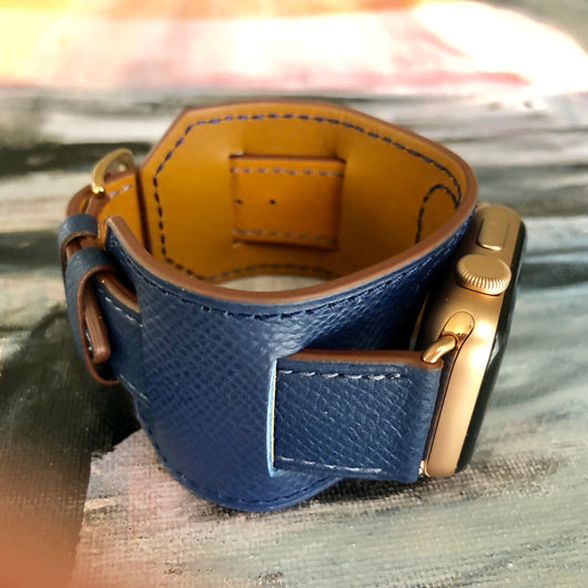 Space Blue Apple Watch Leather Cuff by Juxli Home.  Handmade, stylish leather strap with rose gold hardware on a 40mm Apple watch on a canvas with a black and gray painting.