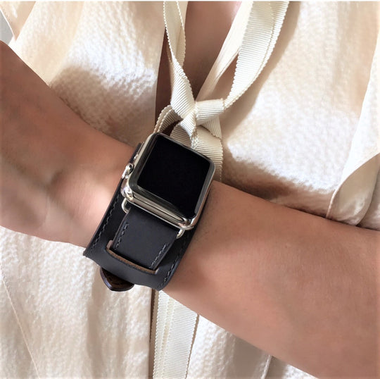 Dark Gray Apple Watch Leather Cuff by Juxli Home.  Handmade, stylish leather strap with rose gold hardware on a 40mm Apple watch on a canvas with a black and gray painting.