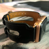 Black Double Buckle Apple Watch Leather Cuff by Juxli Home.  Handmade, stylish leather strap with rose gold hardware on a 40mm Apple watch on a canvas with a black and gray painting.