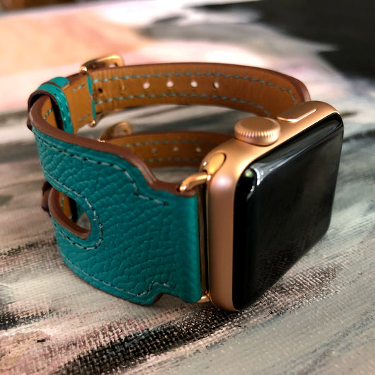 Sea Green Apple Watch Double Buckle Leather Cuff by Juxli Home.  Handmade, stylish leather strap with rose gold hardware on a 40mm Apple watch on a canvas with a black and gray painting.