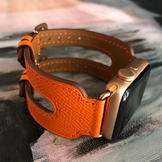 Summer Orange Double Buckle Apple Watch Leather Cuff by Juxli Home.  Handmade, stylish leather strap with rose gold hardware on a 40mm Apple watch on a canvas with a black and gray painting.