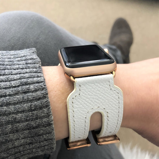 White Apple Watch Double Buckle Leather Cuff by Juxli Home.  Handmade, stylish leather strap with rose gold hardware on a 40mm Apple watch on a canvas with a black and gray painting.