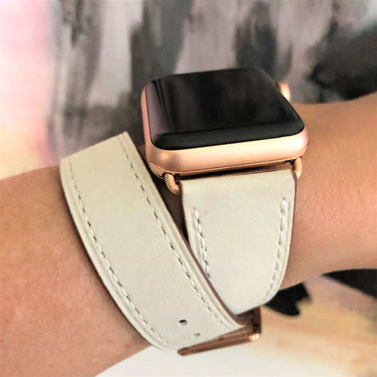 Women's Ivory Double Wrap Apple Watch Leather Band by Juxli Home.  Handmade, stylish leather strap with rose gold hardware on a 40mm Apple watch on a canvas with a black and gray painting.
