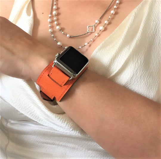 Summer Orange Apple Watch Leather Cuff by Juxli Home.  Handmade, stylish leather strap with rose gold hardware on a 40mm Apple watch on a canvas with a black and gray painting.