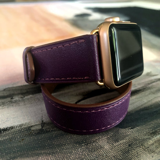 Rasin Purple Double Wrap Apple Watch Band by Juxli Home.  Handmade, stylish leather strap with rose gold hardware on a 40mm Apple watch on a canvas with a black and gray painting.