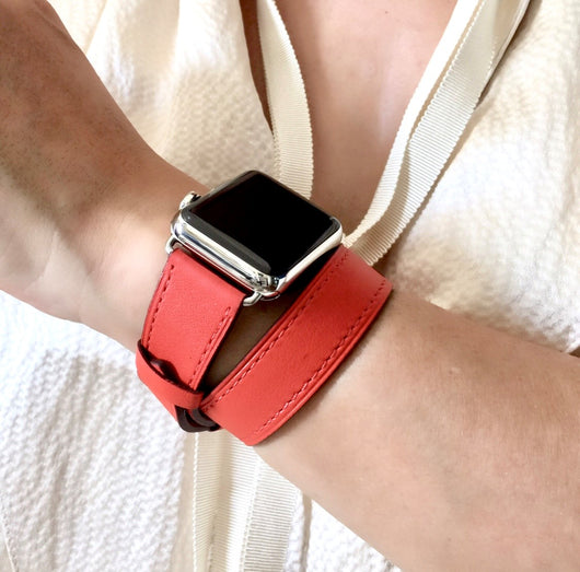 Fire Red Double Wrap Apple Watch Leather Band by Juxli Home.  Handmade, stylish leather strap with rose gold hardware on a 40mm Apple watch on a canvas with a black and gray painting.