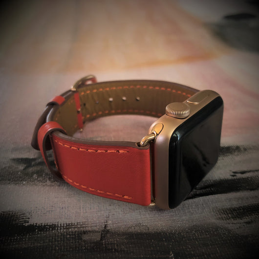 Fire Red Apple Watch Band by Juxli Home.  Handmade, stylish leather strap with rose gold hardware on a 40mm Apple watch on a canvas with a black and gray painting.