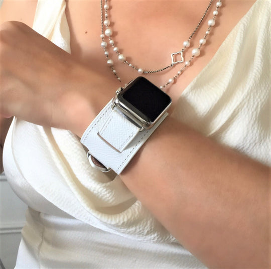 White Apple Watch Leather Cuff by Juxli Home.  Handmade, stylish leather strap with rose gold hardware on a 40mm Apple watch on a canvas with a black and gray painting.