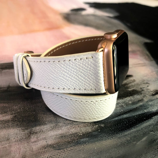 Textured Leather White Double Wrap Apple Watch Band by Juxli Home.  Handmade, stylish leather strap with rose gold hardware on a 40mm Apple watch on a canvas with a black and gray painting.