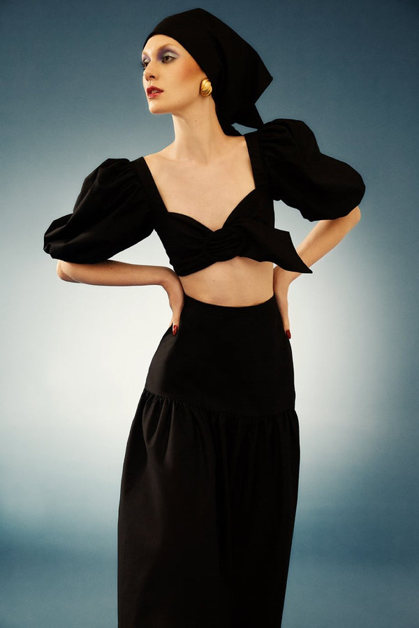 This top cropped features a detachable belt with a large buckle and charming puffed sleeves