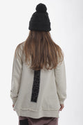 Women ivory tunic sweatshirt with black cracks print patch