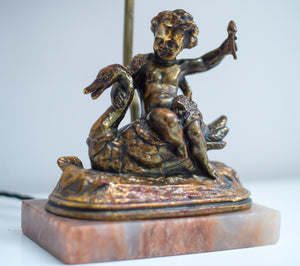 A gilt composition cherub figural table lamp cherub seated on a swan