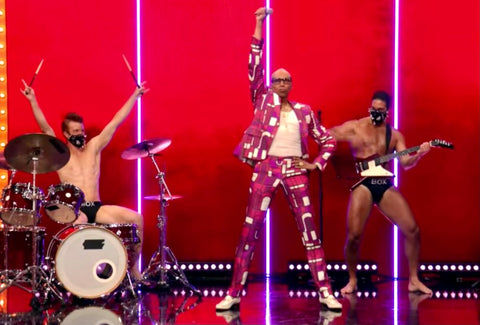 RuPaul dances on stage with box boys playing instruments