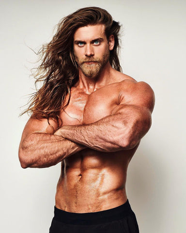 Brock O'Hurn topless with flowing hair on the beach