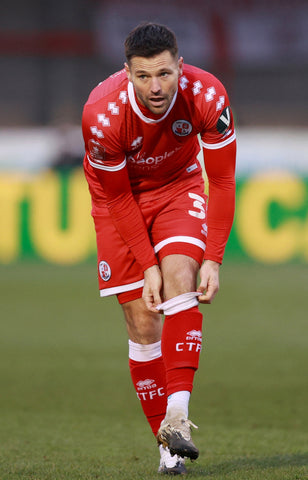 Mark Wright pulling up sock in red crawley town kit