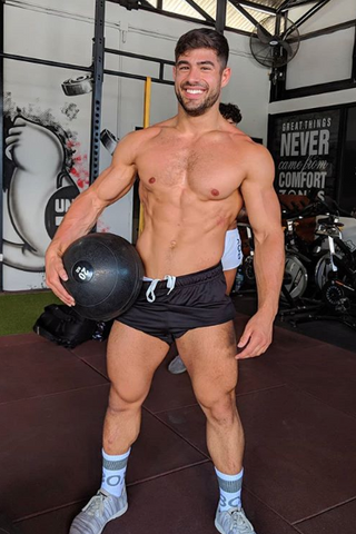 Box model in small black shorts holds medicine ball