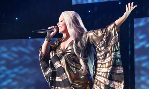 Demi Lovato sings on stage blonde hair glamourous dress