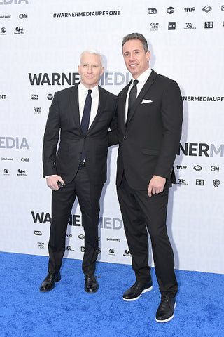 Chris Cuomo and Anderson Cooper in suits on blue carpet