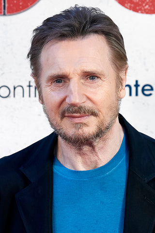 liam neeson with beard and blue tshirt and jacket